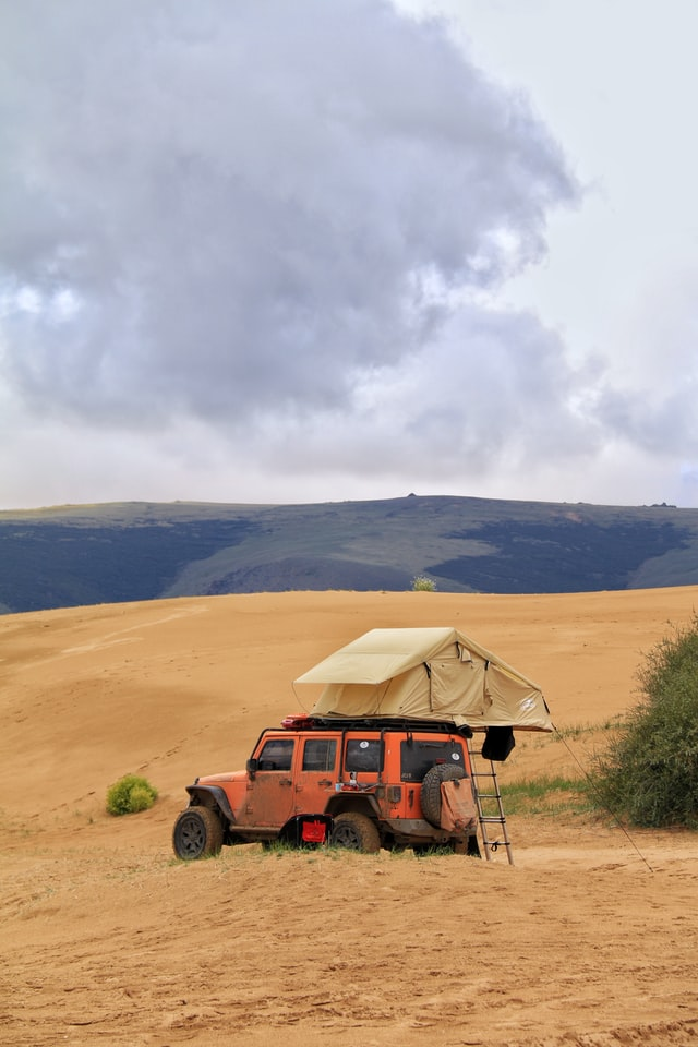 the orange truck has a tent on it for camping